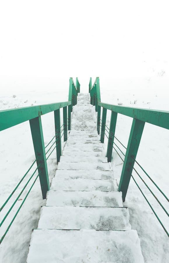 Trappa till ingenstansbegreppet gröna räcke och moment i snö Sikt till vitt utrymme arkivbilder
