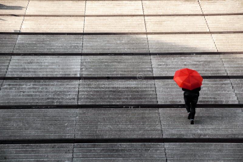 Trappafotgängare med det röda paraplyet royaltyfri fotografi