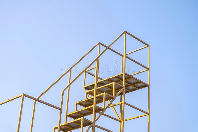 Trappan för ledstånggulingstål med bakgrund för blå himmel arkivfoton