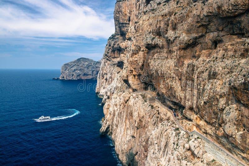 Trappan i kalksten vaggar till stalaktitNeptungrottan Fartyg som lämnar Grotte di Nettuno i Sardinia, Italien arkivfoto