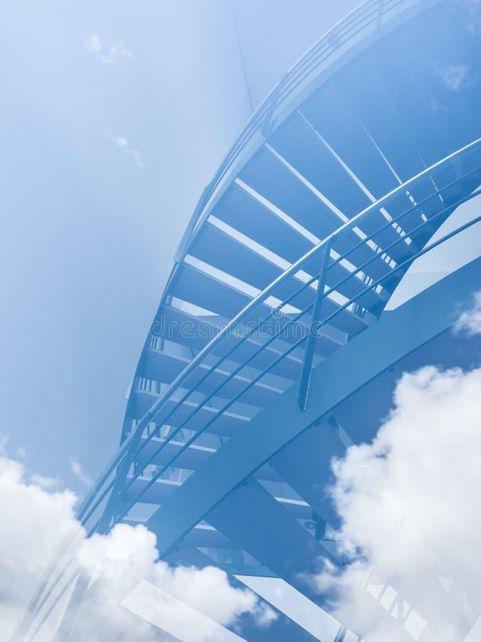Trappan verkar för att leda in i molnen i blå himmel arkivfoton