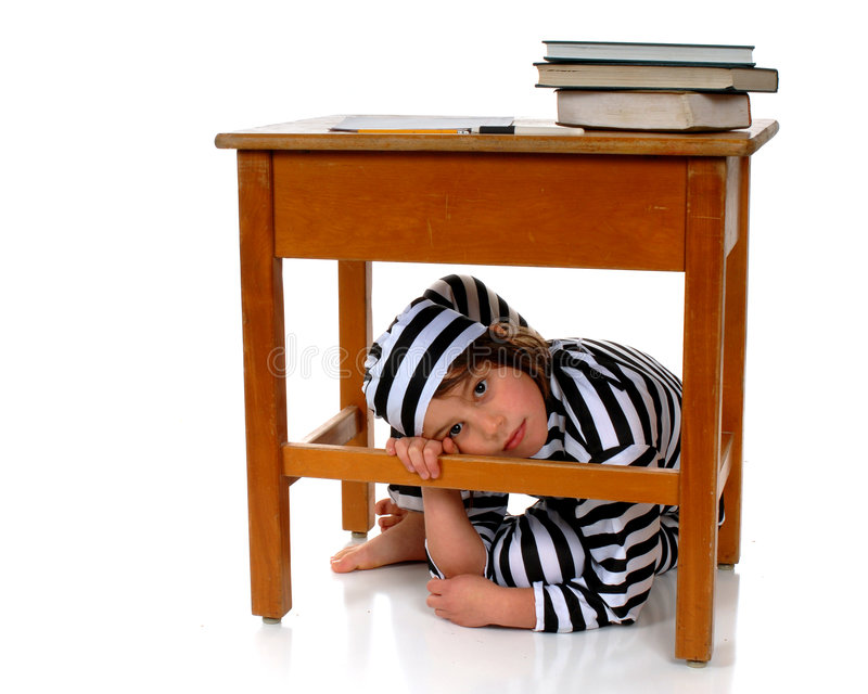 Trapped. Unhappy elementary girl in prison garb hiding under her school desk royalty free stock photography