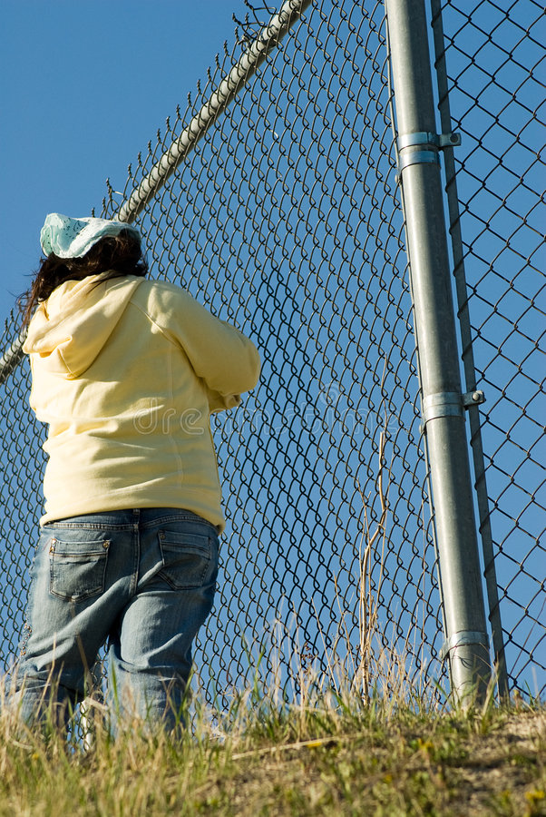 Trapped. A low angle view of a young girl standing by a chain fence royalty free stock photo