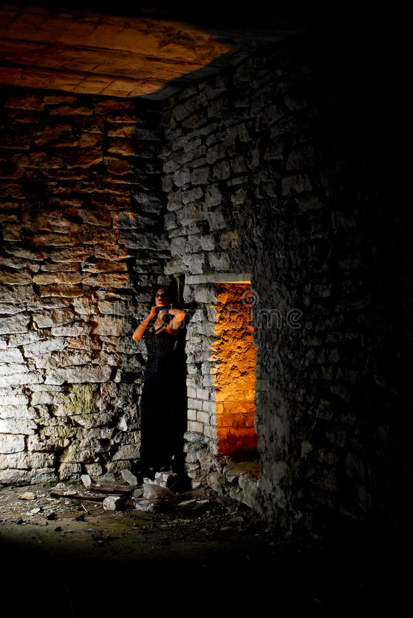 Trapped Goth Girl. A dangerous goth girl chained on a stone wall in ruined premises at night stock image