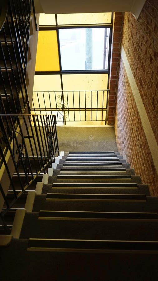 Trappenhuis in een modern woonflatgebouw met warm licht die uit geel gebrandschilderd glasvenster komen royalty-vrije stock fotografie