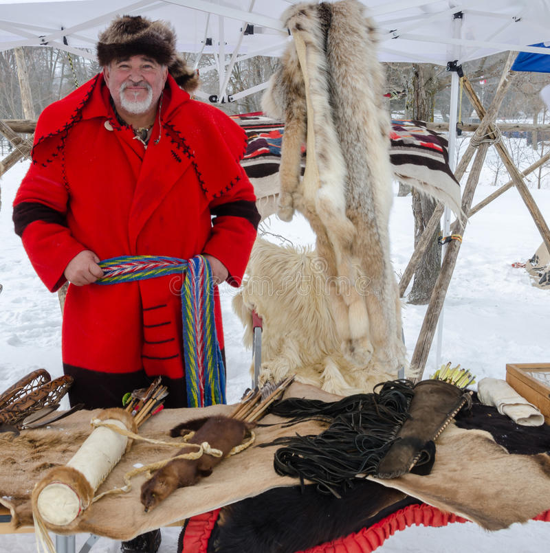 Trapper displaying his furs and pelts. Bearded trapper with beaver hat and red blanket coat displays his pelts and furs at a Canadian winter festival smile royalty free stock image