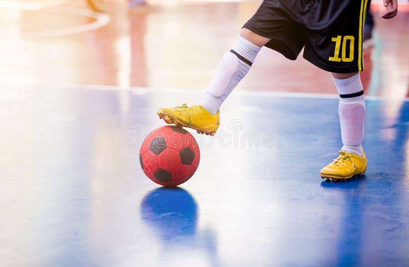 Trappola futsal del giocatore del bambino e controllare la palla per il tiro allo scopo immagine stock