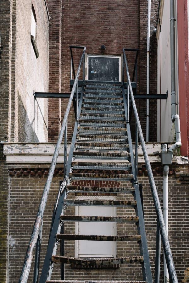 Trappuppgång för brandflykt på en gammal tegelstenbyggnad arkivfoto