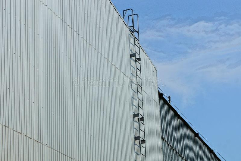 Trappuppgång för långt järn på en grå metallvägg av en industribyggnad mot himlen royaltyfria foton
