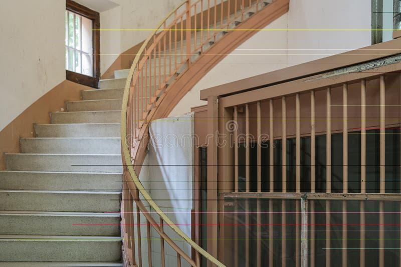 Trappuppgång i fängelse bredvid ett gallerfönster arkivbilder