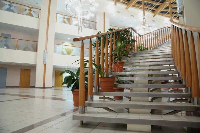 Trappuppgång med trappräcke i stor ljus korridor royaltyfri bild