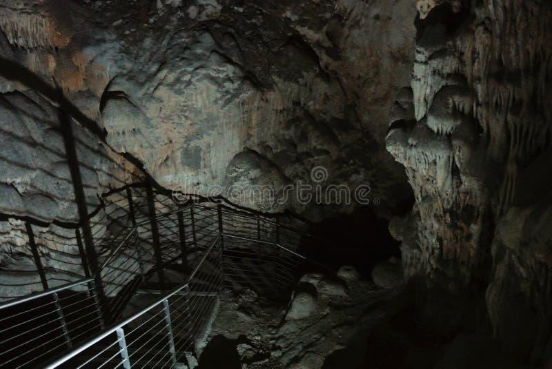 Trappuppgång som djupt går in i grottan, härligt upplyst format royaltyfria bilder
