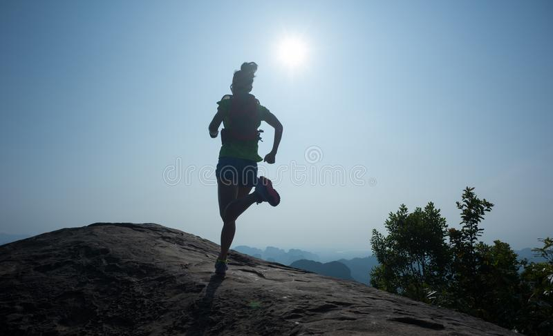 trascini il funzionamento al bordo della scogliera della cima della montagna dell'alba fotografia stock libera da diritti