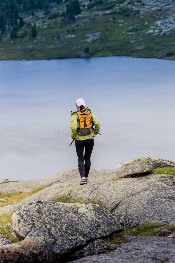 Trascini il paese trasversale della donna corrente in montagne il bello giorno dell'estate immagini stock