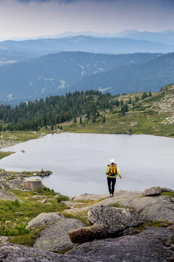 Trascini il paese trasversale della donna corrente in montagne il bello giorno dell'estate fotografia stock libera da diritti