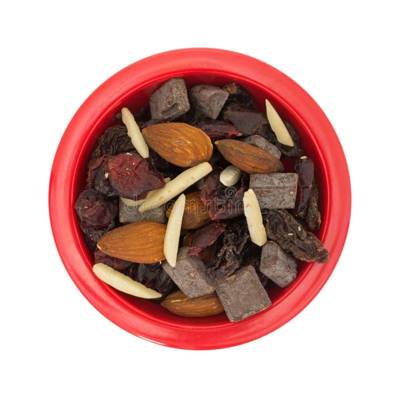 Trascini la miscela con i dadi e la frutta secca in ciotola rossa fotografia stock