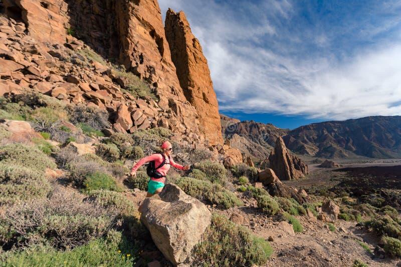 Trascini la ragazza corrente con lo zaino in montagne sul percorso roccioso fotografia stock libera da diritti