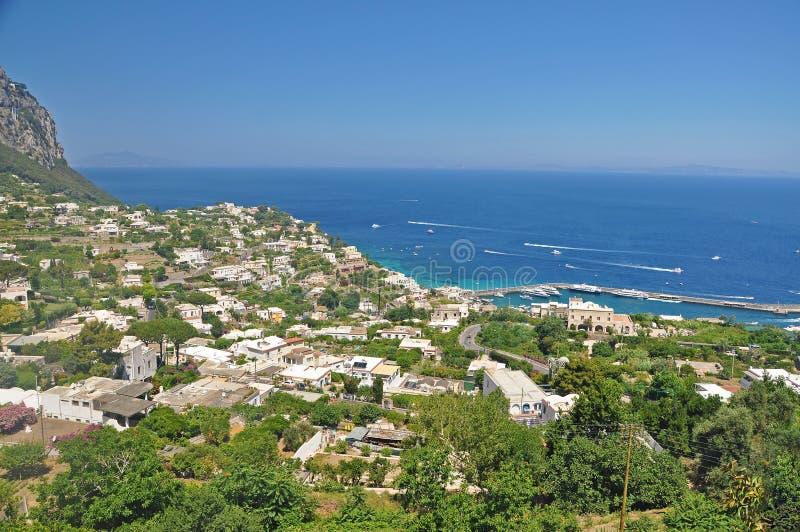 Trascuratezza la città di Capri e del porticciolo sul isla italiano fotografia stock libera da diritti