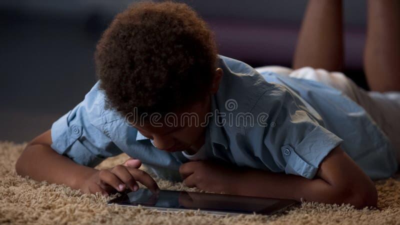 Trascurato dal bambino dei genitori che pratica il surfing sulla compressa che si incoraggia su, chiacchierata online fotografie stock