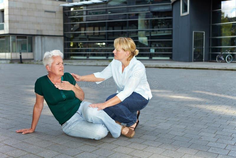 Traseúnte que ayuda a la mujer mayor enferma fotografía de archivo