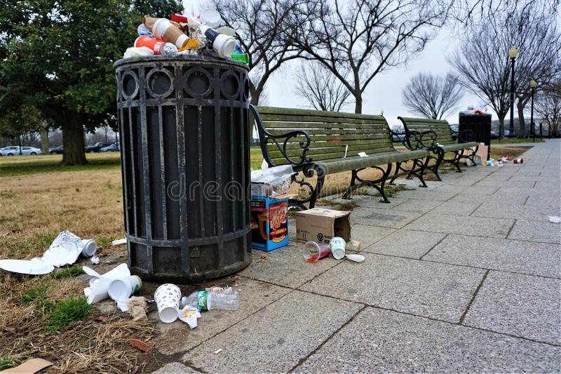 Trash accumulates at the National Mall. Overflowing trash cans and litter spill onto sidewalks and winter yellowed grass. Mildew and algae coat the wood slat royalty free stock photo