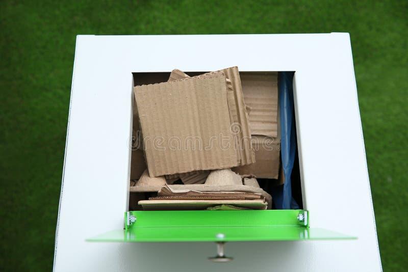 Trash bin with cardboard on color background. Recycling concept. Trash bin with cardboard on color background, closeup. Recycling concept stock images