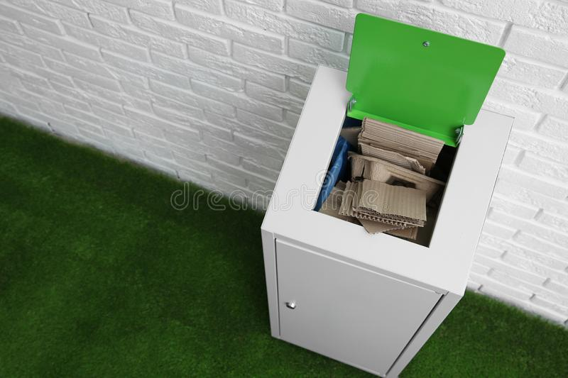 Trash bin with cardboard near brick wall, space for text. Recycling concept. Trash bin with cardboard near brick wall indoors, space for text. Recycling concept stock photography