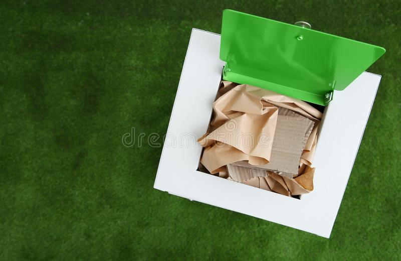 Trash bin with paper and cardboard on color background, space for text. Recycling. Concept royalty free stock photography