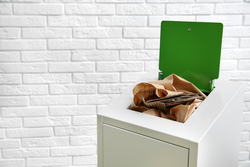 Trash bin with paper and cardboard near wall, space for text. Recycling concept. Trash bin with paper and cardboard near brick wall, space for text. Recycling stock images