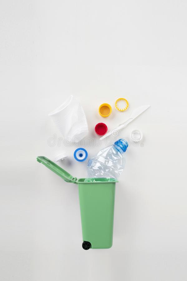 Trash bin with plastic waste on a gray background. Recycling concept stock image
