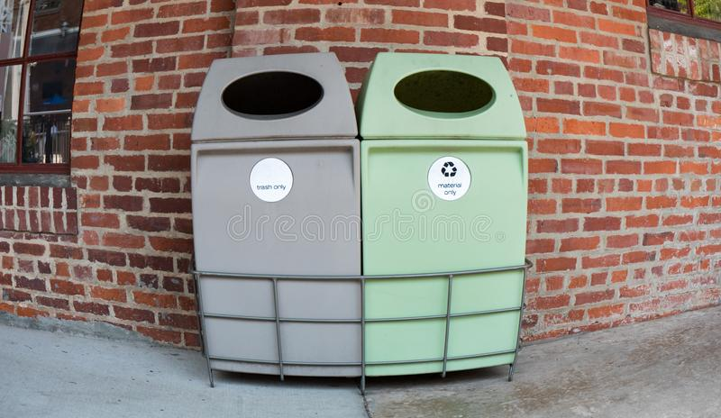 A trash bin and a recycling bin taken with a fish eye lens with a brick background. stock image