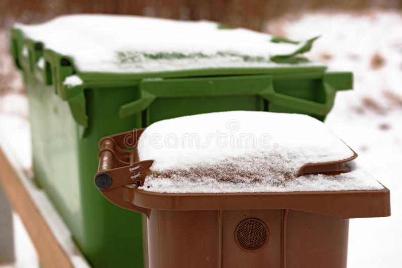 Trash bin with snow. Snow covered brown trash bin lid in winter. Bin has air vent at side stock photos