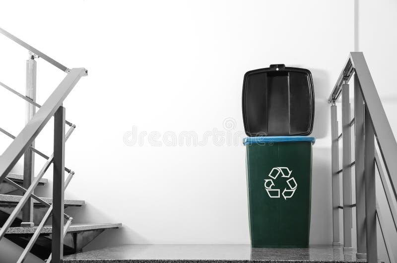 Trash bin on stair landing indoors. stock photography