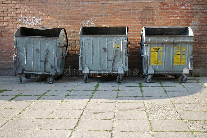 Trash bins. Three metallic trash bins beside the bricks wall royalty free stock image