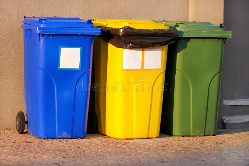 Trash can, garbage bin, recycling bin in tourist complex resort, waiting to be picked up by garbage truck. Blue, yellow and green. royalty free stock photos