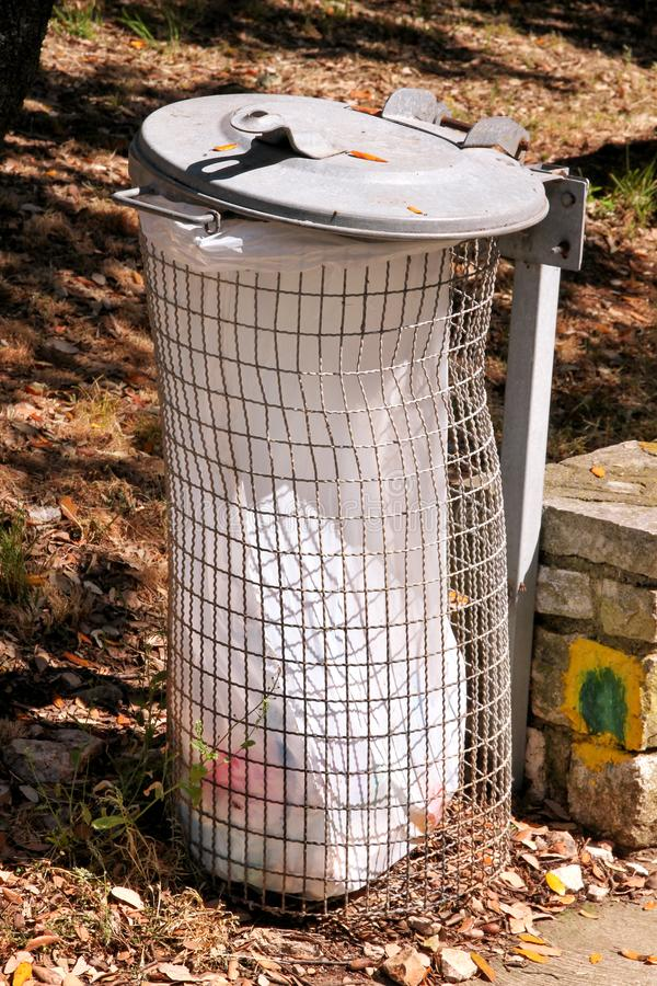 Trash can and recycling bin in park natural outdoor on sunny day. Garbage recycle can and trash bin with white plastic bag. royalty free stock photo