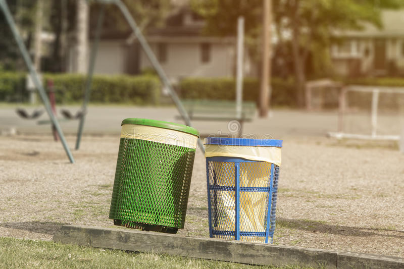 Trash cans in a playground park area with recycling and proper cleanliness. Copyspace on top stock photography
