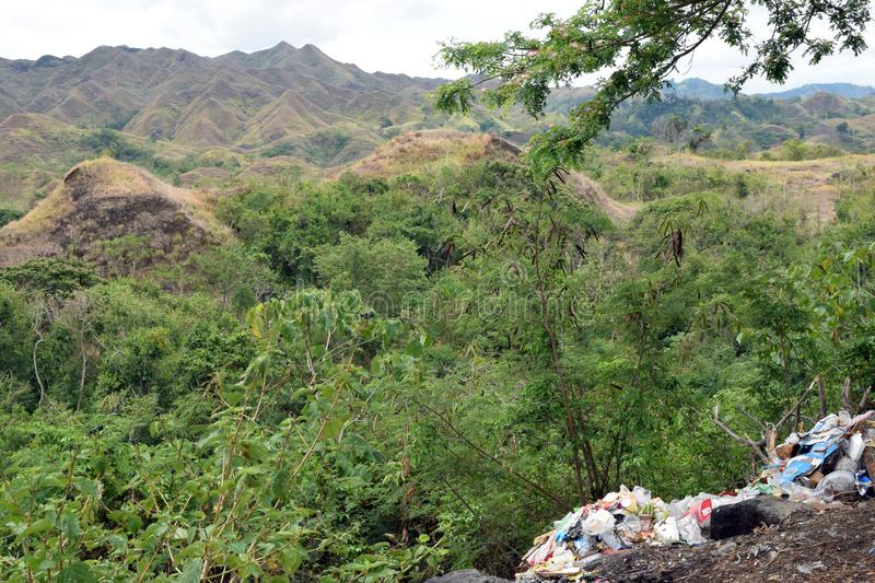 Trash garbage piles thrown along mountain side by uncaring and irresponsible neighborhood stock photo