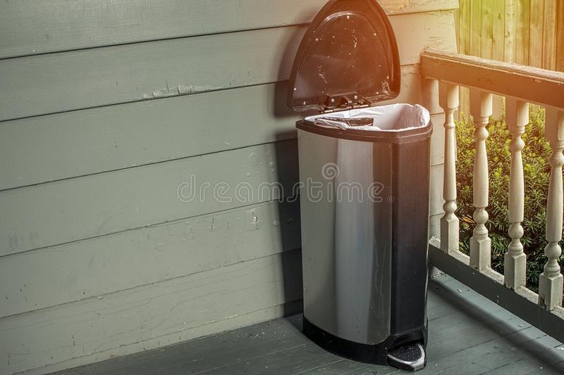 Trash on home porch. Smelly garbage bin outside for removal fro. M house. Room for copyspace stock photo
