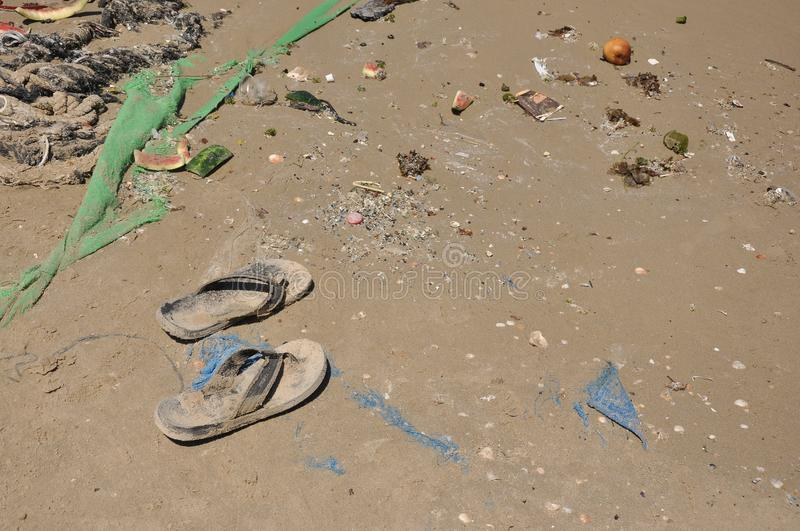 Trash on sand, and a pair of flip flops. Plastic and rop stock photos