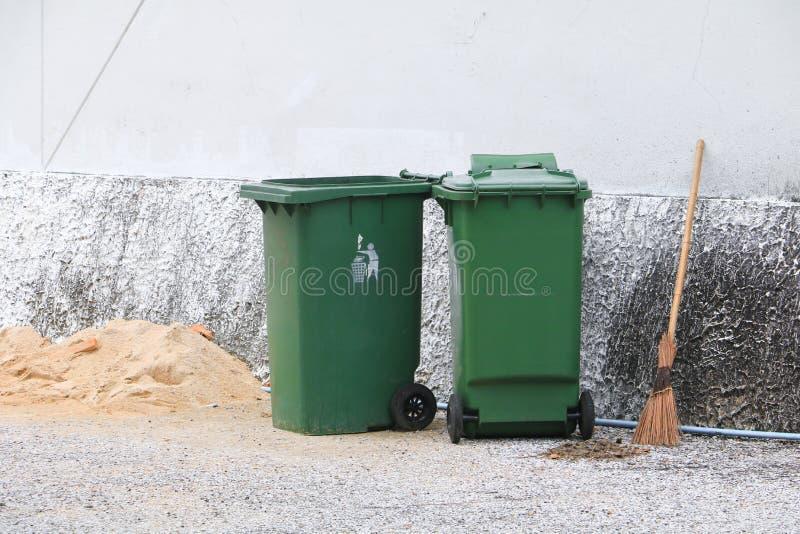 Trashcan esverdeia caixotes de lixo do escaninho dos desperdícios fora da estrada do fundo da parede fotografia de stock royalty free