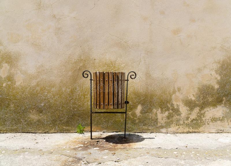 Trashcan next to a sprouting plant in front of a dreary wall - copy space royalty free stock images