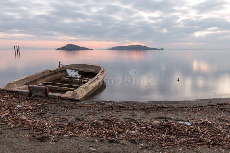 Trasimeno湖翁布里亚美丽的景色黄昏的,与一条小,老小船部分填满由水,完全仍然 库存图片