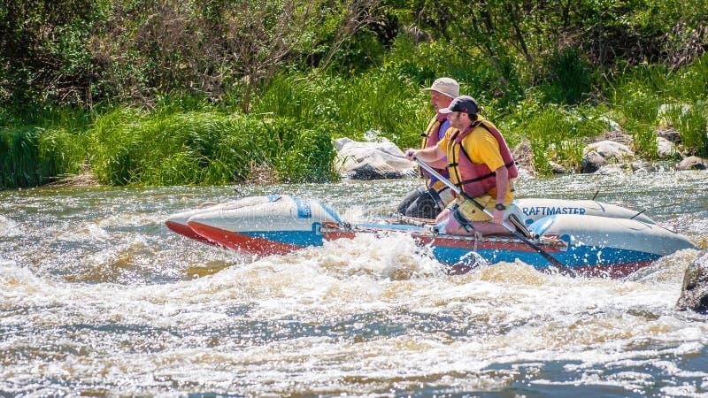 trasportare Due uomini stanno navigando su una barca gonfiabile di gomma teamwork Sport estremo Turismo ecologico dell'acqua fotografia stock