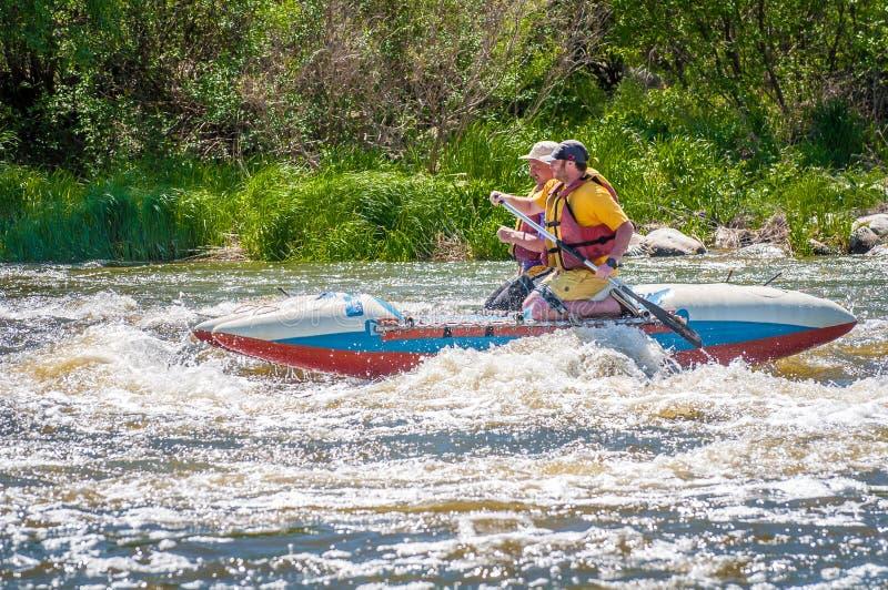 trasportare Due uomini stanno navigando su una barca gonfiabile di gomma teamwork Sport estremo Turismo ecologico dell'acqua immagine stock libera da diritti