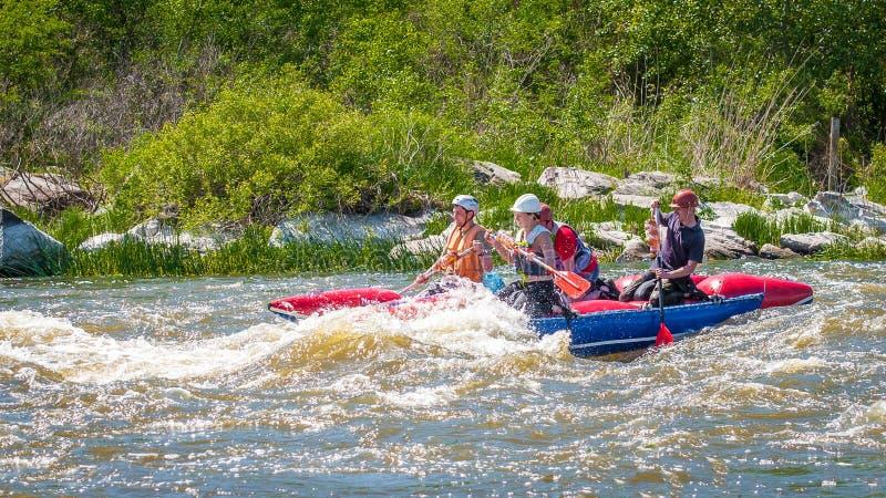 trasportare Società allegra dei giovani che navigano su una barca gonfiabile di gomma teamwork Turismo ecologico dell'acqua fotografia stock libera da diritti