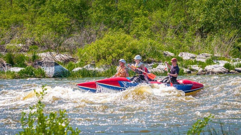 trasportare Società allegra dei giovani che navigano su una barca gonfiabile di gomma teamwork Turismo ecologico dell'acqua immagini stock