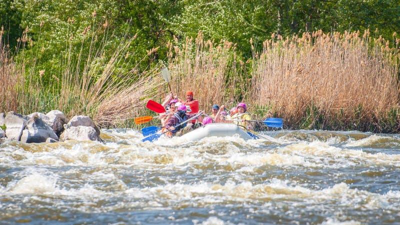 trasportare Società allegra della gente delle età differenti che navigano su una barca gonfiabile di gomma teamwork Emozioni posi fotografia stock