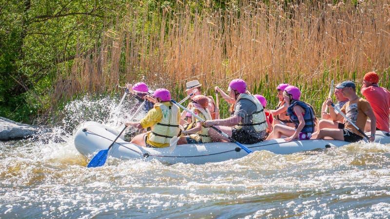 trasportare Società allegra della gente delle età differenti che navigano su una barca gonfiabile di gomma teamwork Emozioni posi immagine stock