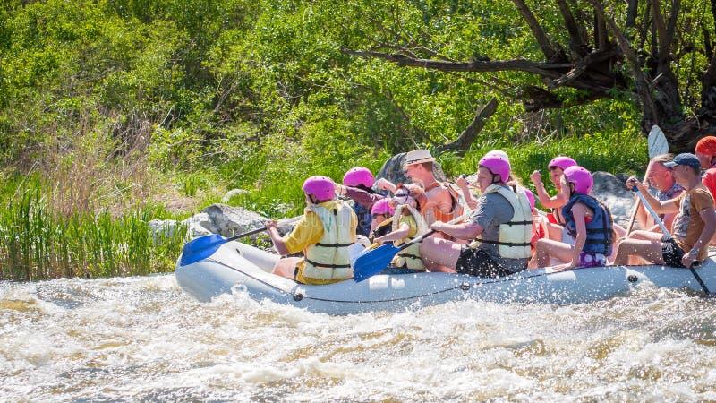 trasportare Società allegra della gente delle età differenti che navigano su una barca gonfiabile di gomma teamwork Emozioni posi fotografie stock libere da diritti